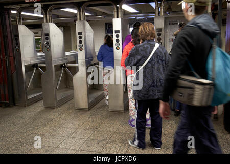 passengers moving through exit turnstiles in subway station New York City USA - Stock Photo