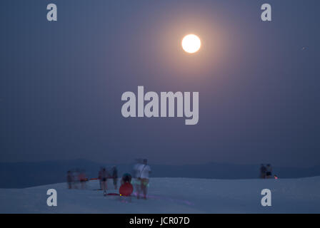 People watching the full moon rise at White Sands National Monument New Mexico, USA. - Stock Photo