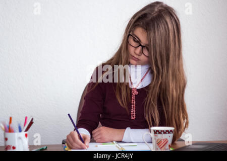 Beautiful cute little blond girl with glasses and purple dress behave serious and take notes in her notebook - Stock Photo