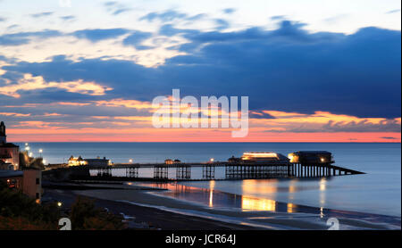The pier illuminted at night as dusk descends over the North Sea, Cromer, North Norfolk, England, Europe - Stock Photo