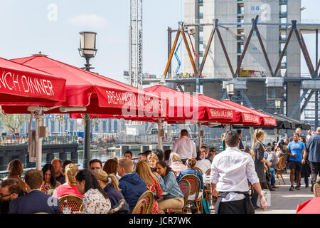 London, UK - May 10, 2017 - Dockside restaurant in Canary Wharf packed with people dining on a sunny day - Stock Photo