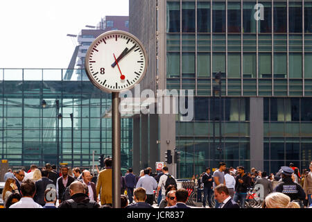 London, UK - May 10, 2017 - A public clock in Reuters Plaza, Canary Wharf packed with people walking through - Stock Photo