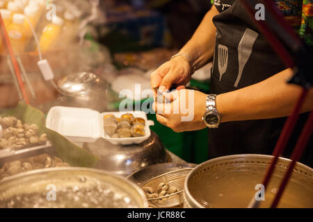 CHIANG MAI, THAILAND - AUGUST 27: Man prepare clams for sale at the Sunday Market (Walking Street) on August 27, - Stock Photo