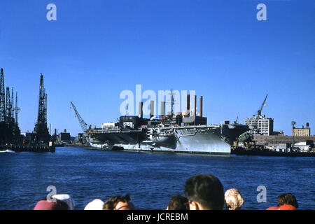 Antique October 1958 photograph, large aircraft carrier at Brooklyn Navy Yard on the East River. The ship is possibly - Stock Photo