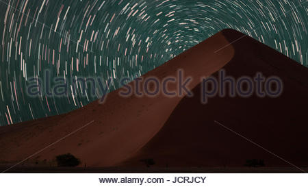 Star trails streak across the sky behind a towering sand dune in the Namib Desert. - Stock Photo