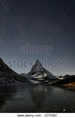 In the evening the Matterhorn (mountain) dominates the skyline. Stars shine bright in the night sky and a frozen - Stock Photo