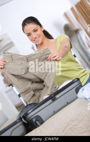 woman packing a luggage for a new journey - Stock Photo