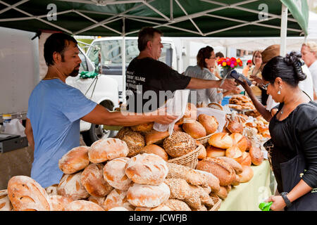 Woman buying loaves of bread at farmers market - USA - Stock Photo