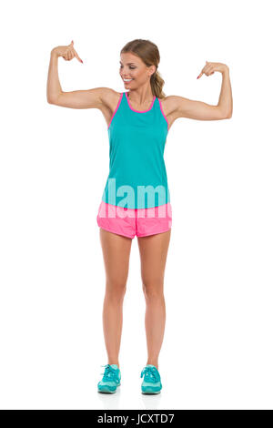 Smiling beautiful young woman in pink shorts, green tank top and sneakers standing with arms outstretched and pointing - Stock Photo