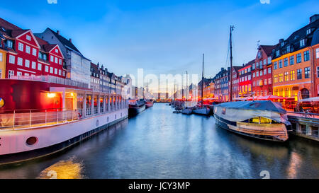 Nyhavn with its picturesque harbor with old sailing ships and colorful facades of old houses in Copenhagen, Denmark. - Stock Photo