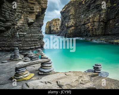 Cairns formed from stacks of pebbles beside turquoise seawater in a natural harbour below Sinclair Girnigoe Castle - Stock Photo