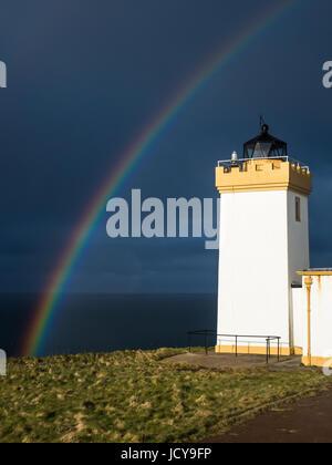 A rainbow frames Duncansby Head Lighthouse near John o' Groats, Scotland. - Stock Photo