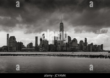 New York City Financial District skyline from across the Hudson River in Black and White. Low storm clouds over - Stock Photo