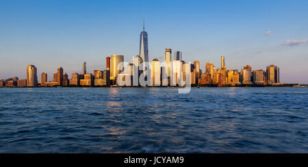 Panoramic of New York City Financial District skyscrapers at sunset - Stock Photo