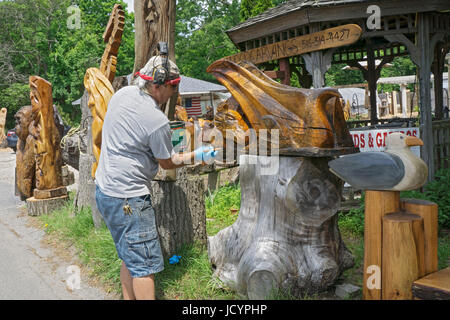 Wood carving artist Fred Steffen varnishing a piece for sale at his roadside stand near the LIE in Manorville, New - Stock Photo