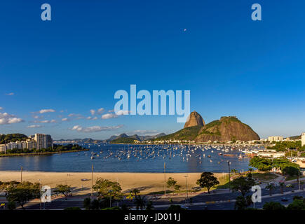 View of Sugar Loaf, Botafogo and Guanabara bay with moon in the sky - Stock Photo