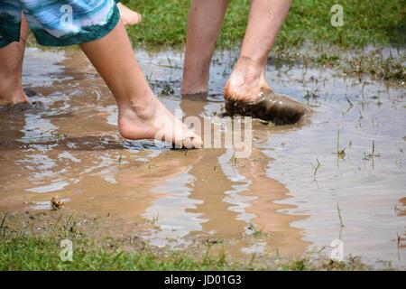 Feet in Muddy Water - Stock Photo