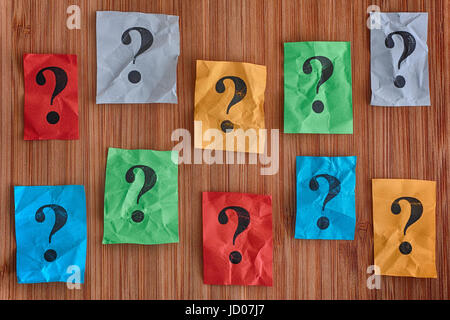 Colorful paper notes with question marks on a wooden background. Concept image. - Stock Photo