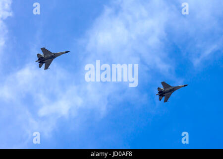 A couple of combat aircrafts flyby in an airshow with blue sky on the background. They are consist of single seat - Stock Photo