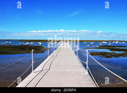 Wooden Harbour Jetty at Ria Formosa with blue sky in background  in Faro Marina, Algarve, Portugal - Stock Photo