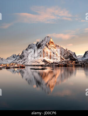 Mount Olstind reflected in the calm waters of Reinfjord on the Lofoten Islands - Stock Photo