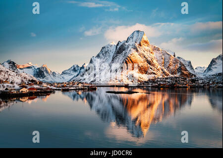Mount Olstind reflected in the calm waters of Reinfjord on the Lofoten Islands