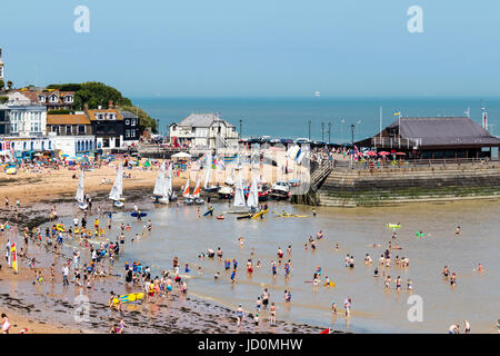 Broadstairs resort town Viking Bay beach. Beach filled with people and many paddling in the shallow water. Sailing - Stock Photo