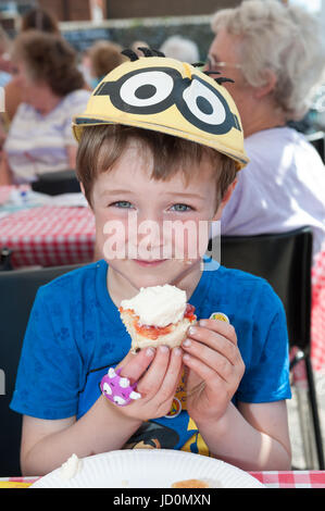 A young boy enjoys eating a scone smothered with jam and cream at a community cream tea party in Wick Village, Littlehampton, - Stock Photo