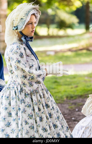 Pretty young teenage, 14-15, woman standing in park dressed up in Victorian costume. White dress with blue flowers and lacy hat tied with big blue ribbon. Side view.
