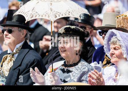 Three people sitting and clapping, all seniors, two women and one man, sitting in bright sunshine all dressed up in upper class Victorian costume as part of the Broadstairs Dicken week festival. Middle woman holding lacey sun parasol.