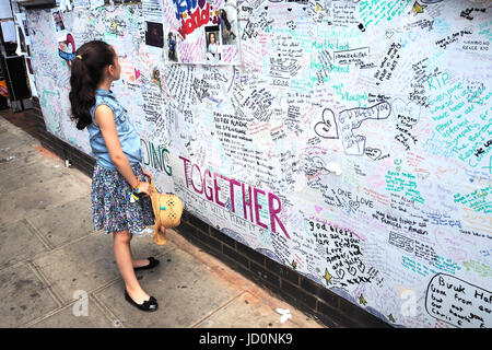London.UK.17th June.2017.A young girl reads the tributes to the victims of the Grenfell Tower disaster in North - Stock Photo