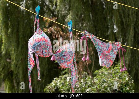 A colorful bikini hanging on a washing line - Stock Photo
