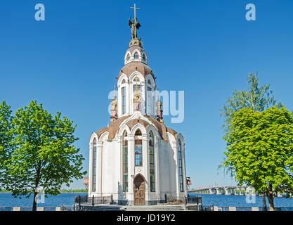 Orthodox temple on the waterfront against the blue sky in the middle spring - Stock Photo