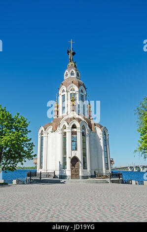 Orthodox temple on the waterfront against the blue sky in end of April - Stock Photo
