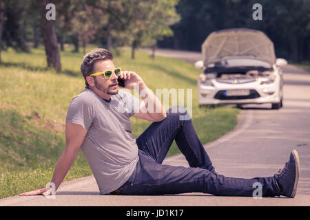 Young modern man sitting on the asphalt and making call with road assistance service. Car with raised hood at the - Stock Photo