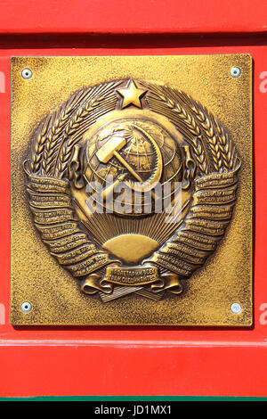 The metal plate at the border post: Golden soviet CCCP - USSR emblem with hammer and sickle on red-green background. - Stock Photo
