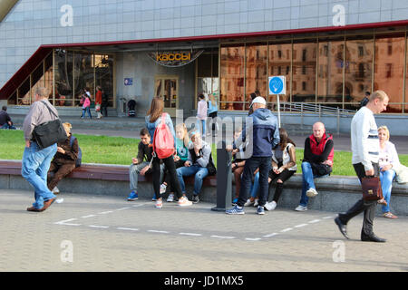 Unidentified young men and women (boys and girls) smoke outside in a specially-designated area for smoking near - Stock Photo