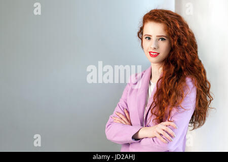 Portrait of successful happy beautiful business woman with red - brown hair and makeup in pink suit. looking at - Stock Photo