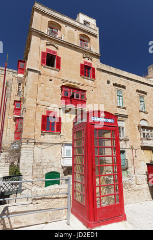English phone booth in front of house with red bay window and red shutters, historic centre, Valletta, Malta - Stock Photo