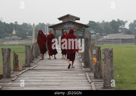 U-Bein Bridge/Amarapura - Myanmar January 22, 2016: Buddhist monks on their daily walk across the bridge in the - Stock Photo