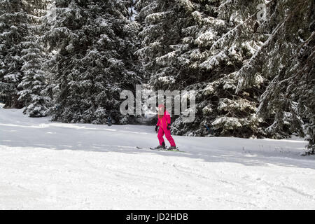 Beautiful cute little blonde girl is on the baby lift with skis on the snow, a nice and sunny day to spend skiing - Stock Photo