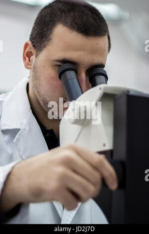 Female medical or scientific researcher man doctor looking through a microscope in a laboratory. Young scientist - Stock Photo