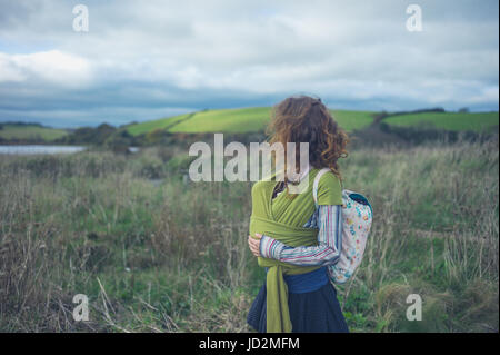 A young mother is walking in the countryside with her baby in a sling - Stock Photo
