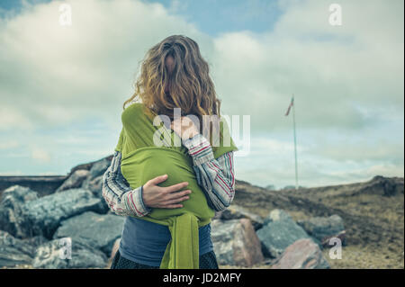 A young mother is standing by some rocks with her baby in a sling and the american flag in the background - Stock Photo
