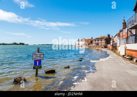 Rising tide flooding the seafront access road, Bosham, a south coast coastal village in Chichester Harbour, West - Stock Photo