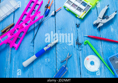 Fishing accessories and tools on a decorative background. Turquoise background. - Stock Photo