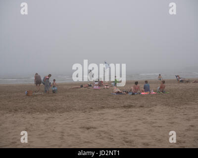 Holiday makers leave a beach at Gruissan,Aude,Languedoc, as a sea mist rapidly descends - Stock Photo