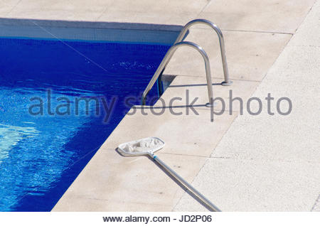 A net used in swimming pool cleaning placed in poolside - Stock Photo