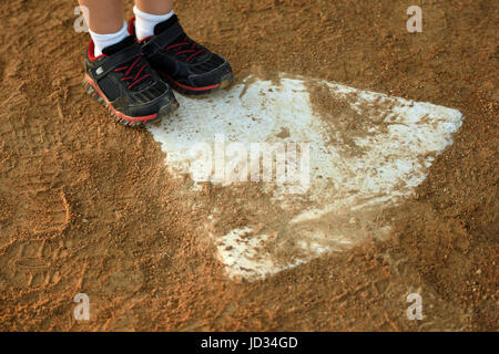 young child makes it to home plate, focused on close up of feet and baseball diamond