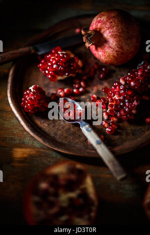 Fresh juicy pomegranate, whole and cut  on vintage background - Stock Photo